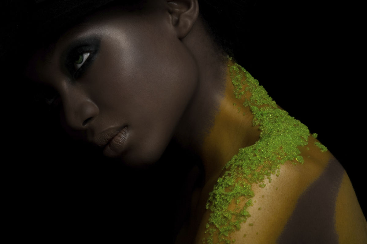 Fashion model with green caviar from Japanese flying fish on her shoulder.